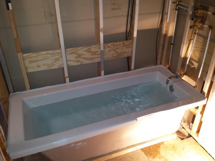 Testen of het allemaal waterdicht is. Dat witte randje langs de badrand is tile beading.