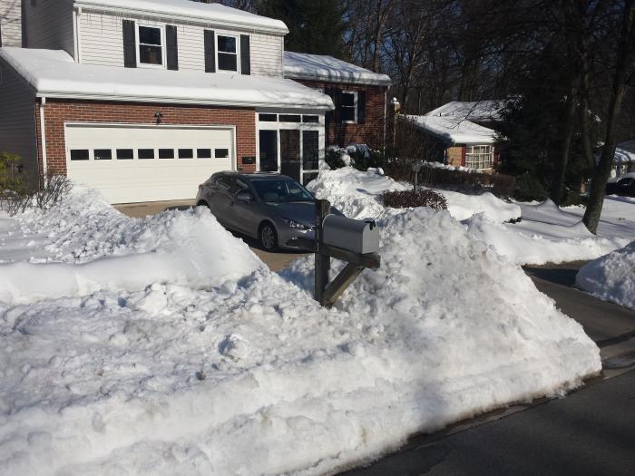 Bergen sneeuw naast de oprit!