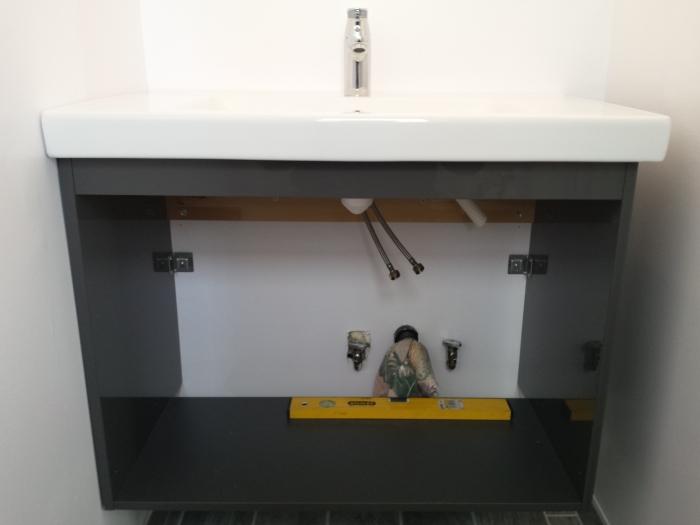 Het monteren van het badmeubel in de badkamer beneden