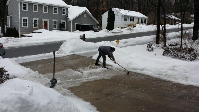 Michiel schoffelt het ijs van de oprit af. Het wordt lente!