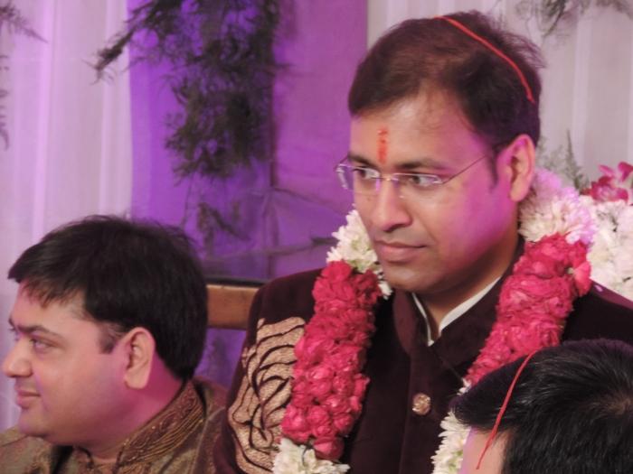 Pranav met touwtje op het hoofd, stip op het voorhoofd, en bloemenketting (allemaal traditie!)